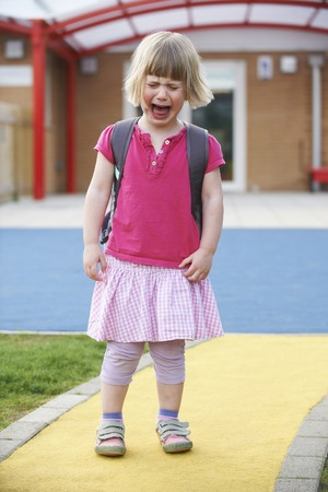 pre school: Little Crying Girl Standing Outside Pre School Building Stock Photo