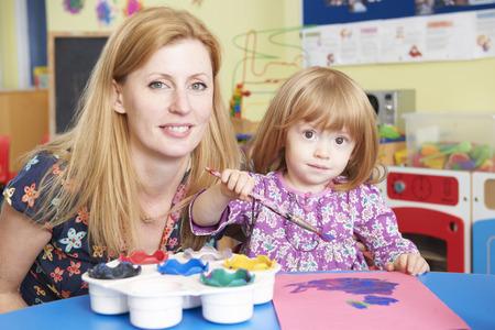 pre school: Teacher Helping Pre School Pupil In Art Class