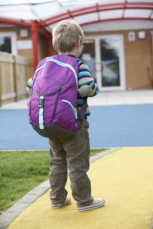 first day: Child Going To School Wearing Backpack Stock Photo