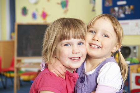 pre school: Two Female Pre School Pupils Hugging One Another Stock Photo