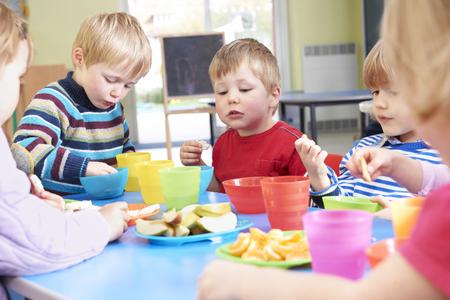 pre school: Pre School Children Eating Healthy Snacks At Breaktime Stock Photo