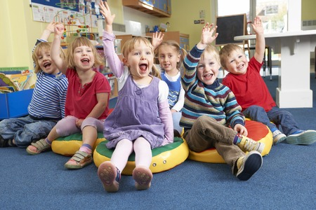 pre school: Group Of Pre School Children Answering Question In Classroom Stock Photo