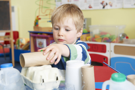 pre school: Boy Building Junk Model In Pre School Class