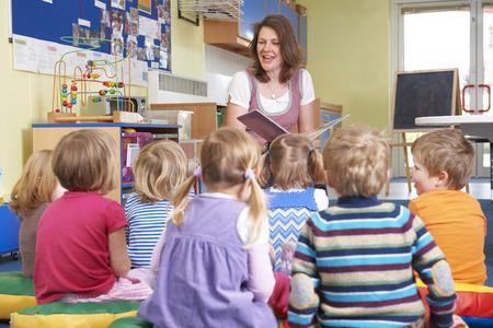 maestra enseñando: Grupo de niños pre entrenamiento que escucha el profesor de Historia de la lectura Foto de archivo