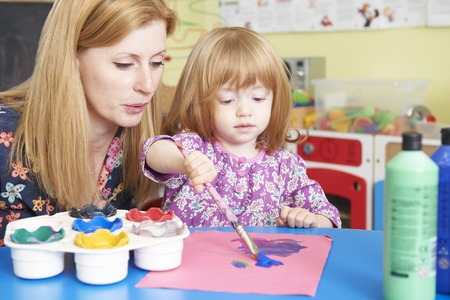 pre school: Teacher Helping Pre School Child In Art Class Stock Photo
