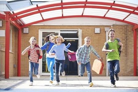 niños saliendo de la escuela: Los escolares que desembocan en patio en el final de la clase Foto de archivo