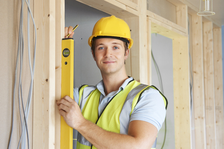 levels: Builder Checking Work With Spirit Level Stock Photo