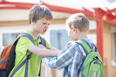 peleando: Dos muchachos que luchan en patio de la escuela