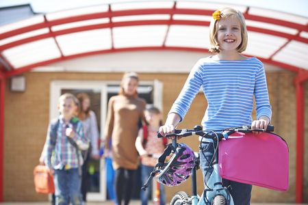 elementary age girls: Female Pupil Pushing Bike At End Of School Day Stock Photo