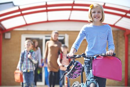 Female Pupil Pushing Bike At End Of School Day 版權商用圖片