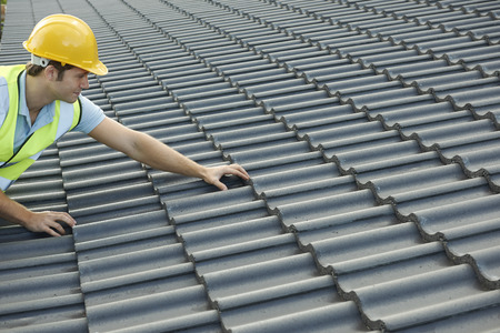 新しい建物の屋根の上のビルダー