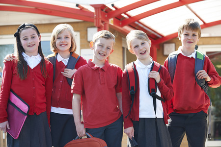 school uniforms: Portrait Of Schoolchildren Outside Classroom Carrying Bags