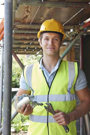 scaffolder: Portrait Of Builder Putting Up Scaffolding Stock Photo