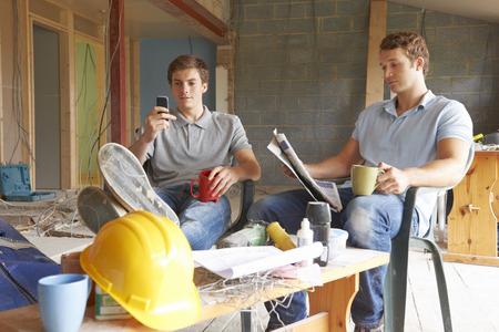 break from work: Builders Relaxing During Break On Site