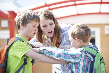 profesor alumno: Profesor Detener Dos muchachos que luchan en patio