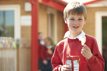 8 years: Boy In School Uniform Eating Potato Chip In Playground