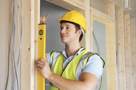 spirit level: Builder Checking Work With Spirit Level Stock Photo