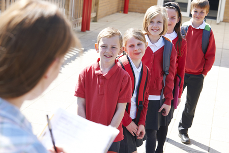 school uniforms: Teacher Taking School Register In Playground Stock Photo