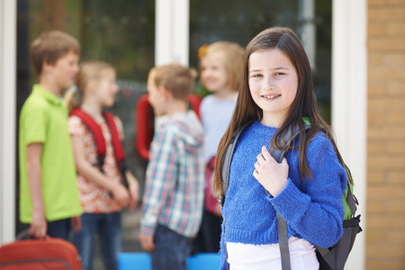 8 years: Girl Standing Outside School With Rucksack Stock Photo