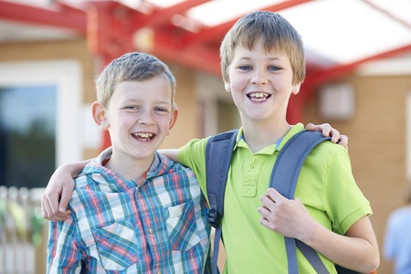 elementary schools: Two Boys Standing Outside School With Book Bags