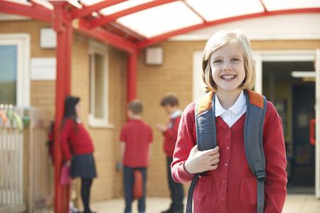 学校の校庭に立っている制服を身に着けている女の子