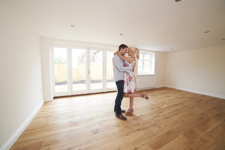 property ladder: Excited Young Couple In Empty Room Of Their First Home