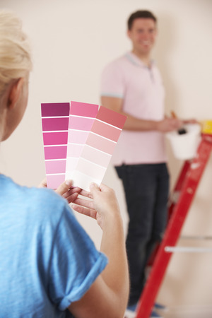 property ladder: Young Couple Looking At Paint Swatches In New Home Stock Photo