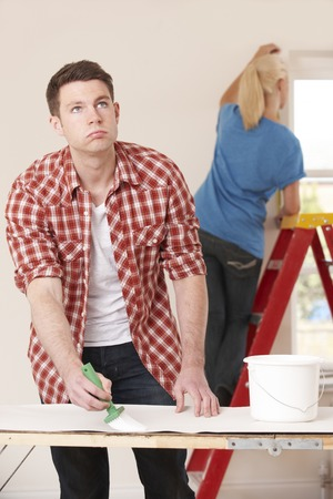 fed up: Young Man Fed Up With Decorating Home Stock Photo