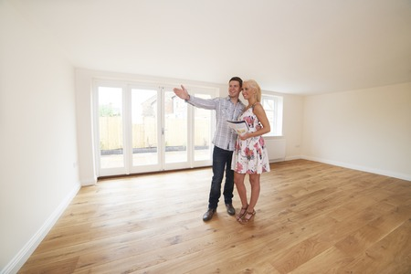 property ladder: Couple With Property Details Looking Around New Home
