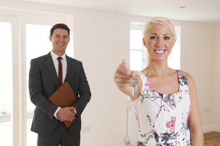 handing over: Estate Agent Handing Over Keys Of New Home To Female Buyer