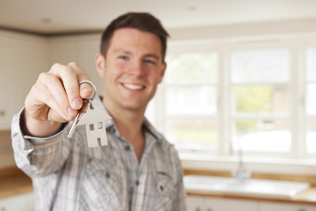 property ladder: Man Moving Into New Home Holding House Shaped Keyring Stock Photo