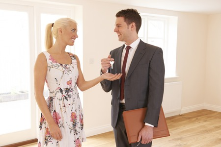 property ladder: Estate Agent Handing Over Keys Of New Home To Female Buyer