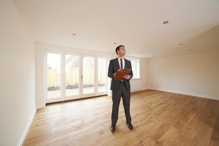 property ladder: Estate Agent Looking Around Vacant New Property