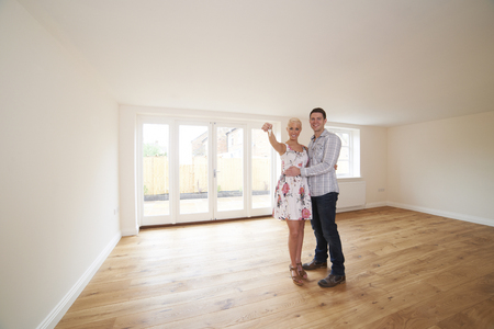 property ladder: Young Couple With Keys To New Home Stock Photo