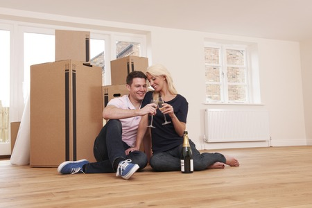 property ladder: Couple Celebrating Moving Into New Home With Champagne