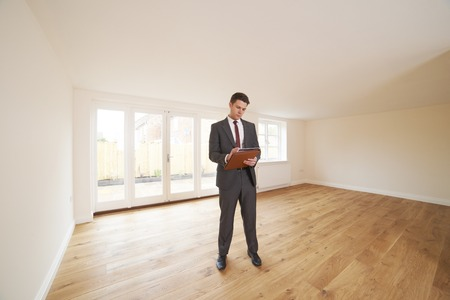 property ladder: Estate Agent Looking At Vacant Property Stock Photo