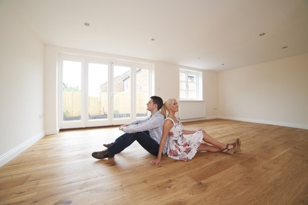 first floor: Young Couple Sitting In Empty Room Of Dream House