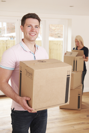 property ladder: Young Couple Unpacking Boxes In New Home