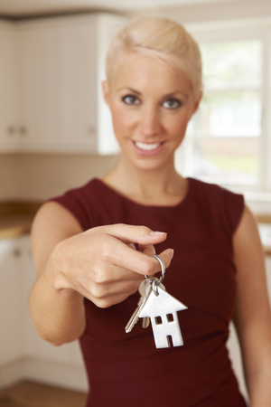 property ladder: Young Woman Holding Keys To New Home
