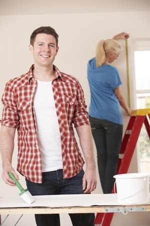 property ladder: Young Couple Decorating New Home Together