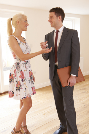 property ladder: Estate Agent Handing Over Keys To Female House Buyer Stock Photo