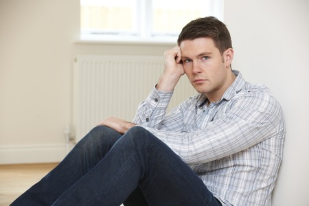 evicted: Depressed Man Sitting On Floor in Empty Room Stock Photo