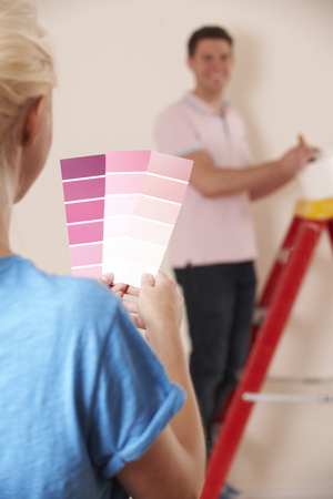 property ladder: Couple Looking At Paint Swatches In New Home