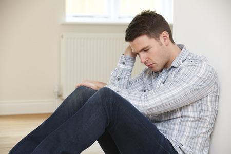 repossession: Depressed Man Sitting On Floor Of Empty Room