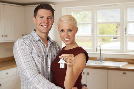 property ladder: Excited Young Couple Holding Keys To New Home Stock Photo