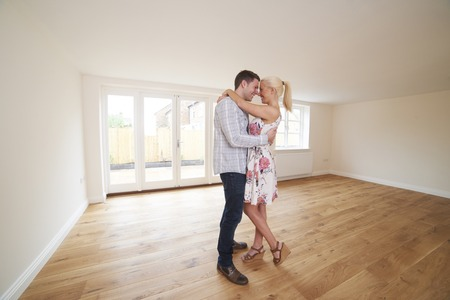 Excited Young Couple In Empty Room Of New Home