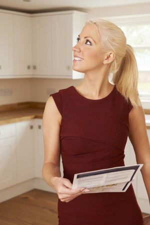 property ladder: Woman Looking At Property Details In New Home
