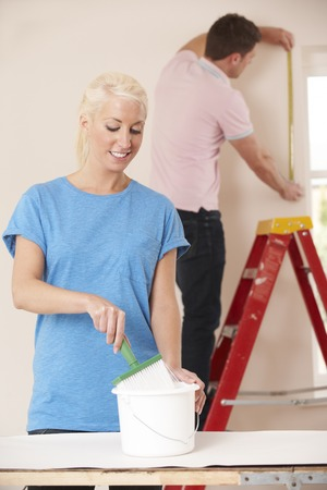 decorating: Young Couple Decorating Home Together