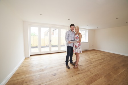 property ladder: Young Couple Looking At Property Details For New Home
