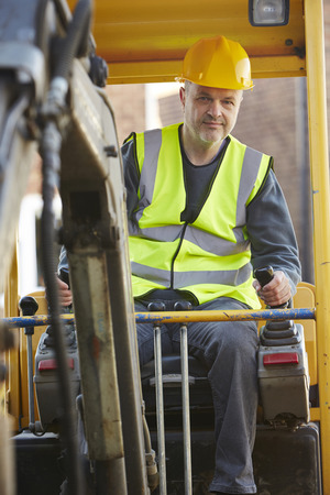 digger: Construction Worker Operating Digger On Site Stock Photo